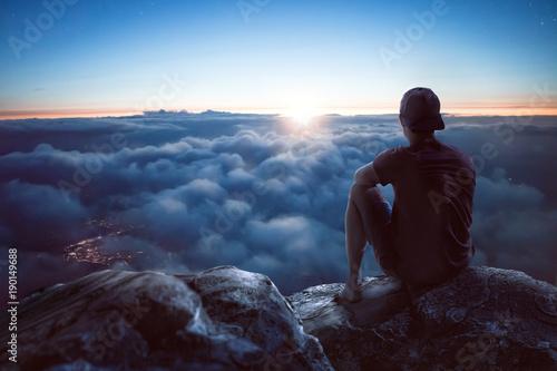 Obraz Junger Mann mit weitem Blick über die Wolken - fototapety do salonu