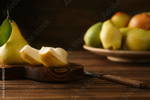 Wooden board with cut pear on table