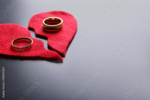 Fabric heart cut in half with wedding rings on grey background Canvas Print