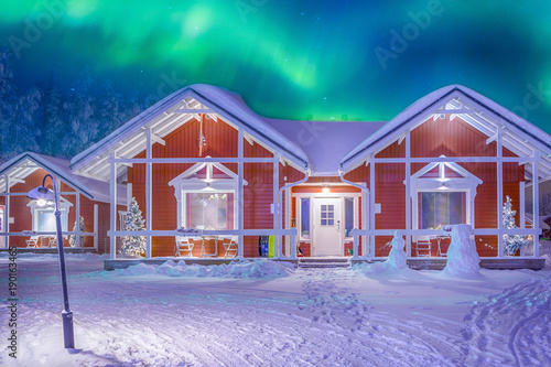 Poster Scandinavië Travel Destinations Concepts. Beautiful Multicoloured Vibrant Aurora Borealis known as Northern Lights Playing with Vivid Colors Over Traditional Lapland Houses in Finland.