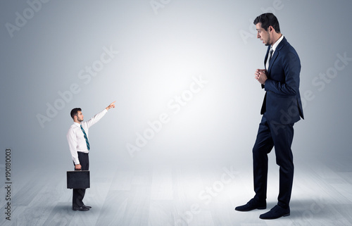 Small businessman pointing to a giant businessman Fototapete