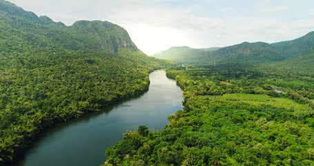 Aerial view of river in tropical green forest with mountains in background