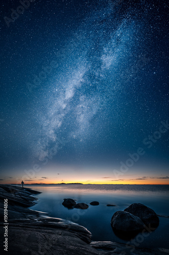Foto op Canvas Nachtblauw Beautiful view of milky way glowing on the sky with calm sea and a man looking at the stars and sunset