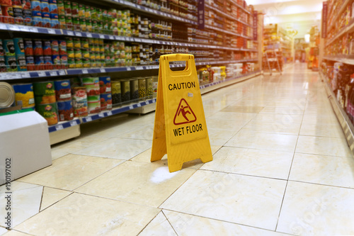 Obraz Yellow sign - caution. Wet floor is in the supermarket against the background of blurry products standing on the shelves - fototapety do salonu