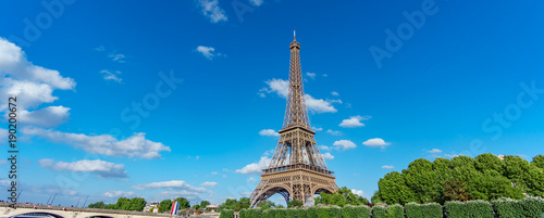 Deurstickers Eiffeltoren The Eiffel Tower panorama over trees, blue sky