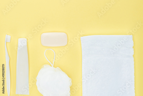 Tela top view of white toothbrush, toothpaste, towel, washcloth and soap, isolated on