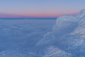 Beautiful sunset above clouds in snow covered Low Tatras mountains during susnet in winter