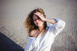 lovely young woman with curly hair, the romance of youth, a journey walk on a warm summer sunny day on a sandy beach with water