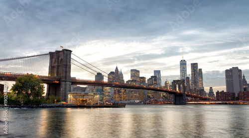 Photo Stands New York Manhattan skyline and Brooklyn Bridge view from Brooklyn Bridge Park at sunset, New York City