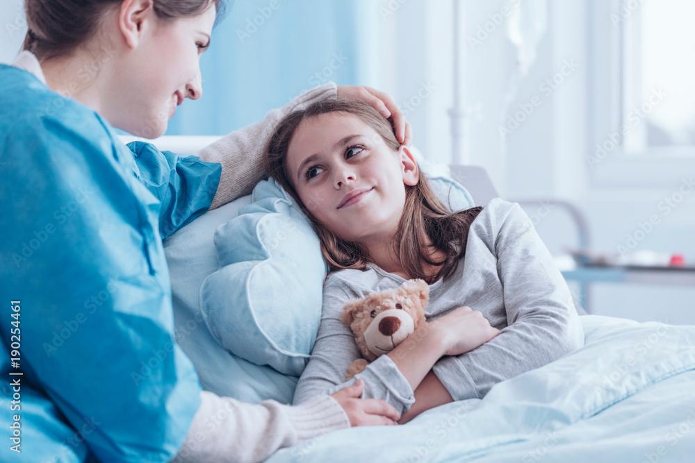 Fototapeta Smiling caregiver visiting sick child