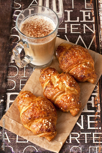 Wall Murals Cafe Fresh croissants and coffee cups for breakfast on wooden vintage table
