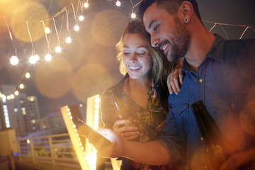 Couple having a drink at rooftop party and using smartphone