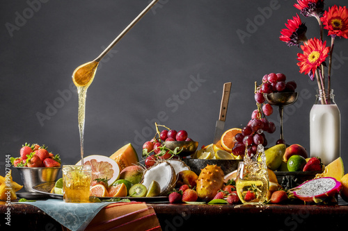 Cuadros en Lienzo Fruit and honey still life with strawberry splashing in champagne glass
