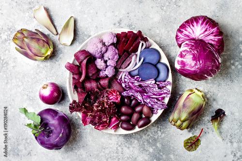 Foto  Purple Buddha bowl with spiral carrots, cauliflower, beet, onion, potato, shredded red cabbage, radicchio salad, kalamata olives