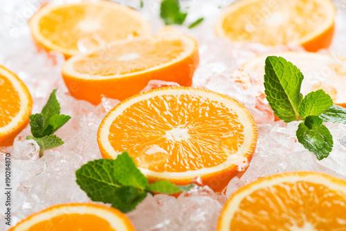 Segments of orange fruits and ice.