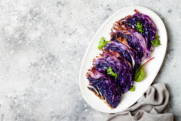 Vegan roasted red cabbage steaks on grey concrete background. Top view, flat lay