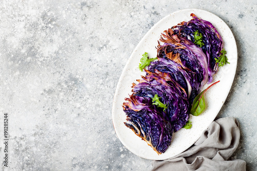 Photo Stands Ready meals Vegan roasted red cabbage steaks on grey concrete background. Top view, flat lay