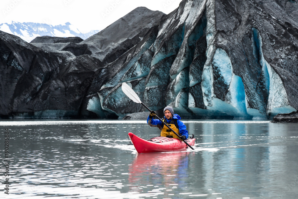 Valokuva  Kayaker paddling away from dark, moraine covered glacier in Alaska