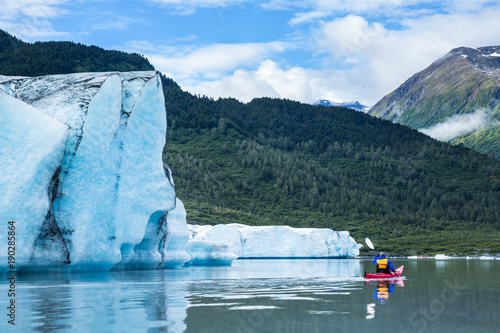 Valokuva  Kayaker paddling away from terminal face of the Spencer Glacier in Alaska