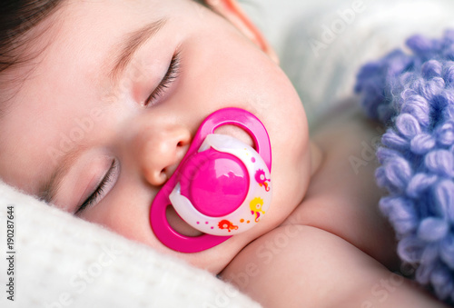 Vászonkép Sleeping Baby with a Pacifier in his Mouth