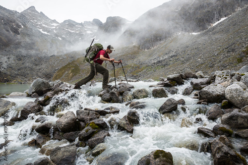 Fototapeta Hiker with large pack crossing a rocky river obraz
