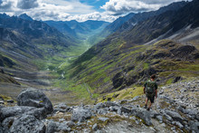 Hiker Descending Steep Rocky Trail Above Glacial Valley In Alaska