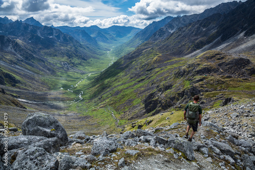 Hiker descending steep rocky trail above glacial valley in Alaska