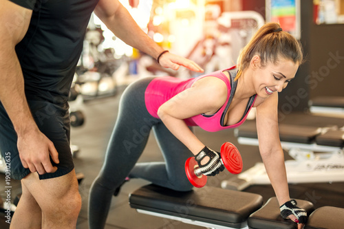 Beautiful woman at the gym with personal trainer
