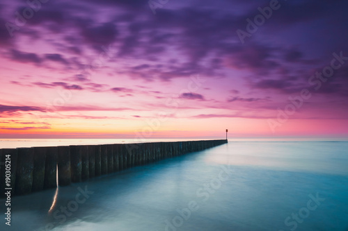 In de dag Aubergine Sunset on the beach with a wooden breakwater, purple tone