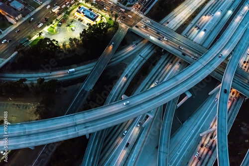 Cuadros en Lienzo Aerial view of a massive highway in Los Angeles, CA at night with young woman ho