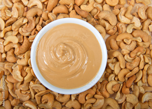 Fotografie, Obraz  White bowl with fresh cashew butter surrounded by cashew nuts