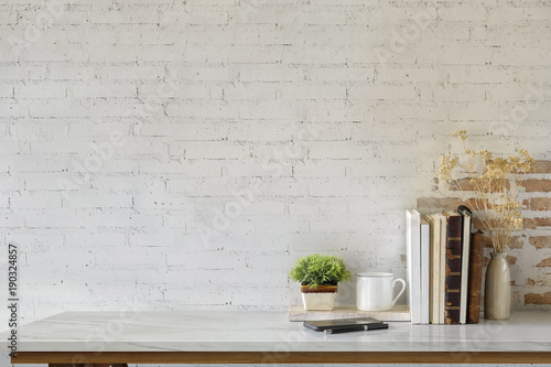 Marble desk with books, coffee mug, mobile phone and plant Canvas Print