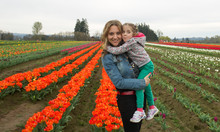 Portrait Close-up Of Four Years Old Cute Girl Is Hugging Her Beautiful Young Mother, Looks At Camera And Smiling, Tulip Field At The Background, Early Spring, Tulip Farm, Oregon USA