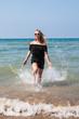 Blond teenager girl on the beach near sea
