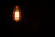 Caged Bulb Glowing In Dark