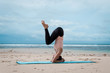 Young woman practice balance asanas on Summer yoga session on beach. Headstand