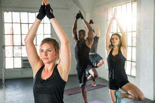 Fotografía  Female power yoga aerobic instructor leader with unisex class raising arms with