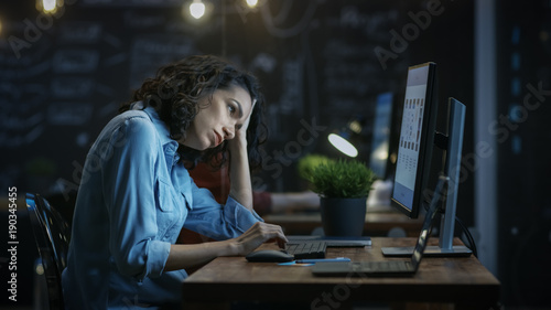 Tired, Overworked Female Financier Holds Her Head in Hands while Working on a Personal Computer Canvas Print