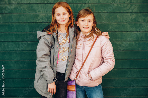 Outdoor Portrait Of Two Cute Little Teen Girls Wearing Warm Jackets Posing Against Green Background Fashion For Children Stock Photo Adobe
