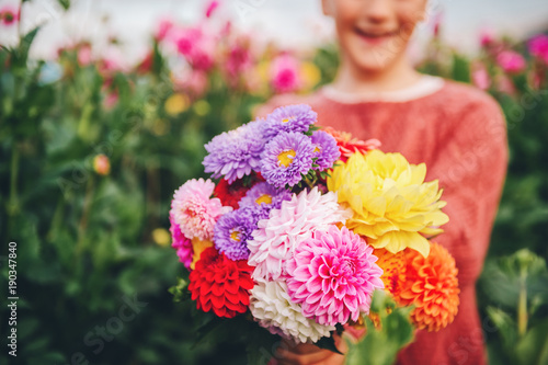 Poster Dahlia Close up image of colorful dahlia and chrysanthemum flowers bouquet holding by a child