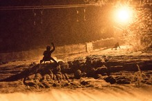 Silhouette Of A Man Sledging A...