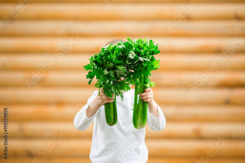 Young boy holding fresh celery in background. Healthy Eating.