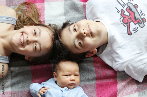 Teenager boy and his young sister lying with their newborn blother smiling and looking at camera. Family concept