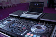 Dj mixes the track in the nightclub at party . Headphones in foreground and DJ hands in motion . PC monitor . Netbook .