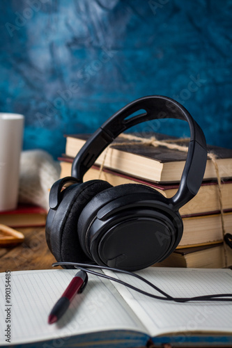 Valokuva  Books are stacked, Headphones, White Cup, open Diary on a wooden background
