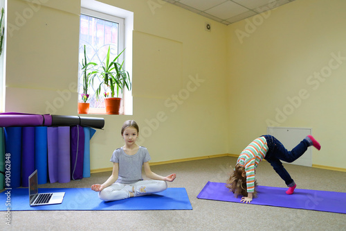 Beautiful blonde girl sits on floor taking lotus pose. Long hair of child neatly combed and collected in tail, on floor covered with mat for fitness, laptop beside and under wall stained multi-colored
