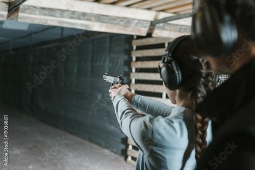 Tela rear view of girl shooting with gun in shooting gallery