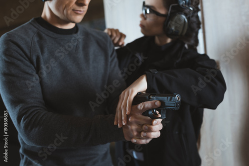 Fototapety, obrazy: cropped image of instructor describing client how to hold gun