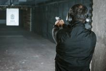Rear View Of Man Aiming Gun At...