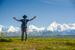 man with outstreched arms in front of Alaskan Range, Denali